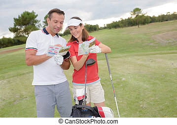 Couple on golf course looking at leaflet