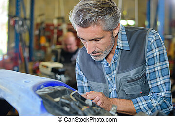 mechanic working on car body