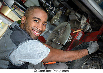 mechanic posing in front of a car