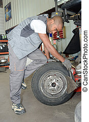 worker fixing a tire