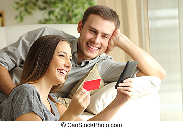 Happy couple buying online with credit card and smart phone...