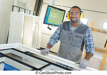 Male worker manufacturing windows