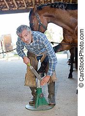 Portriat of farrier filing horse's hoof