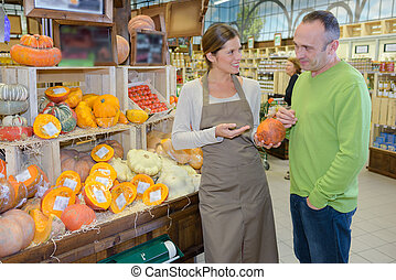 Shop assistant showing pumpkin to customer