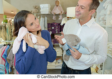 Woman holding cuddly toy to face, man laughing