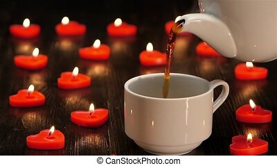 White cup with hot coffee on background of burning candles