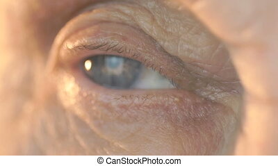Close-up of blue eye of a woman aged 80s