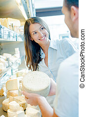 Male shop worker showing whole cheese to customer