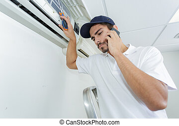young handyman repairing air conditioning system calling for...