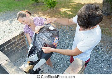 Couple tipping charcoal on to barbeque