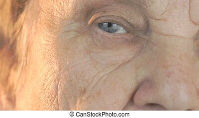 Elderly woman opening and closing eyes. Close up