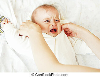 Mother carrying clothers for baby todler little son crying,...