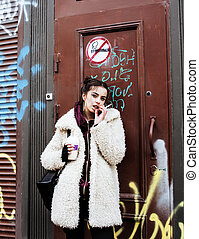 young pretty stylish teenage girl outside at city wall with...
