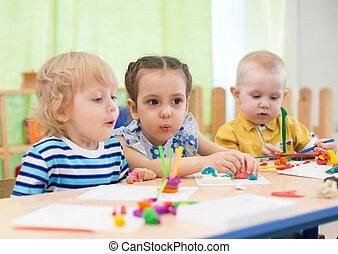 kids doing cake in day care centre - kids modeling cake in...