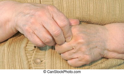 Elderly woman makes massages their of hands