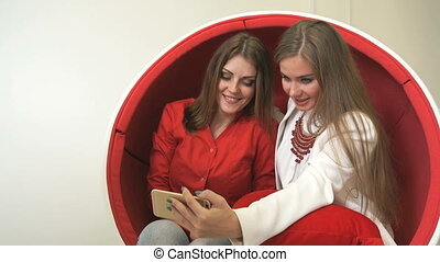 Two women sitting in red chair, making selfies - Attractive...