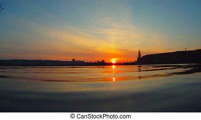 Stone falls into water - Beautiful sunset on a calm lake....