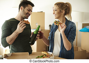 Couple enojying some drinks and takeout pizza