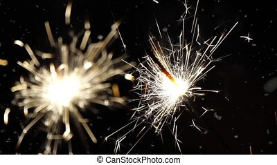 Firework sparkler burning with dancing snowflakes against black night sky background. Winter time blizzard.