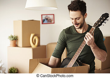Man unpacking guitar from the cardboard box