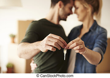 Young couple holding up new house key