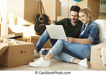 Couple with laptop around cardboard boxes