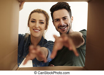Young couple with reaching hands and carton