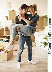 Young man carrying woman in their new accommodation