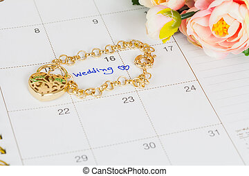 word wedding on calendar and gold bracelet with heart
