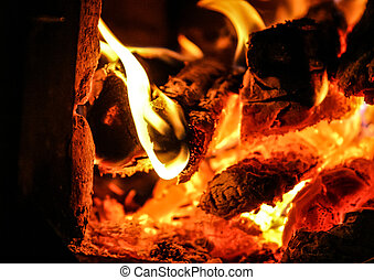 Fire burning inside a brick stove - wood, ash, flames.