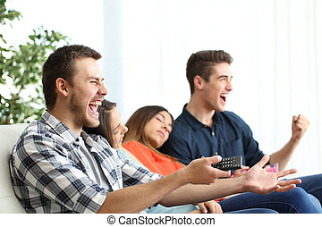Excited men watching tv and bored girlfriends
