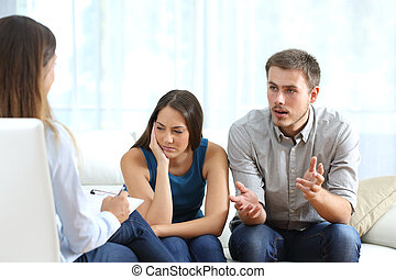 Angry and sad couple talking with a marriage counselor -...