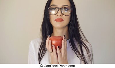 Cute brunette in glasses holding and looking on red apple in...