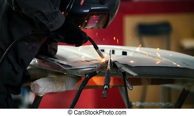 Welding industrial: worker in helmet repair detail in car...