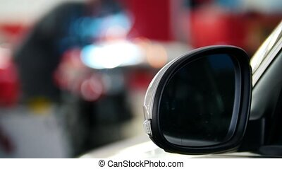 Defocused background - car service - worker grinding metal...