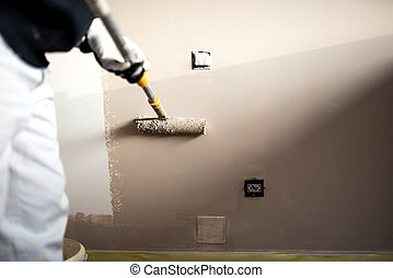 Handy man decorating walls with paint. Construction plaster worker painting and renovating with professional tools
