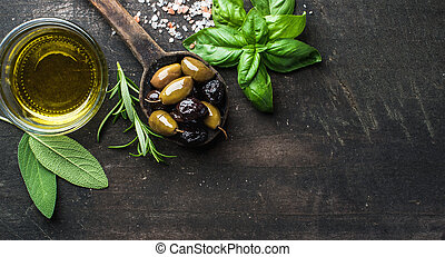 Green and black Mediterranean olives in old cooking spoon...