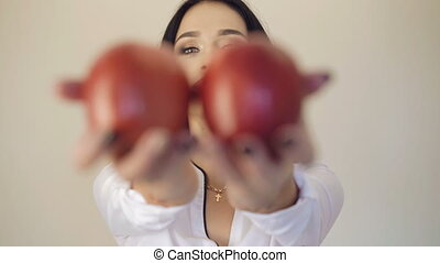 Girl's hands holds two big red apples in front of camera,...