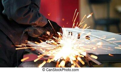 Professional car service - worker grinding metal...