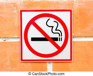 non smoking sign on brick wall
