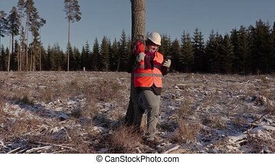 Lumberjack with chainsaw laughing near tree in forest
