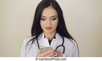 Attractive female doctor using mobile phone on background...