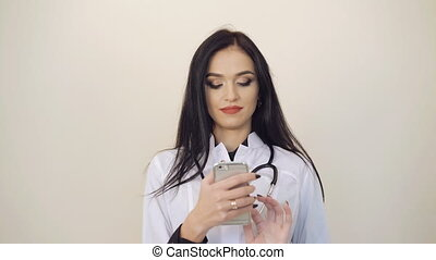Pretty female doctor using mobile phone on background. 4K.