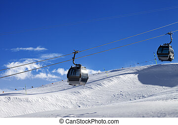 Gondola lifts on ski resort at sun wind day. Greater...