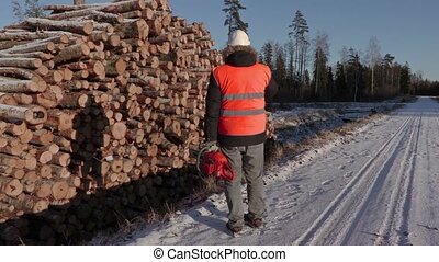 Lumberjack with chainsaw talking on phone near snow covered...
