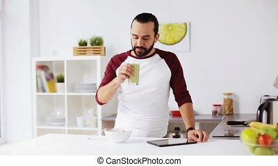 man with tablet pc eating breakfast at home - vegetarian...