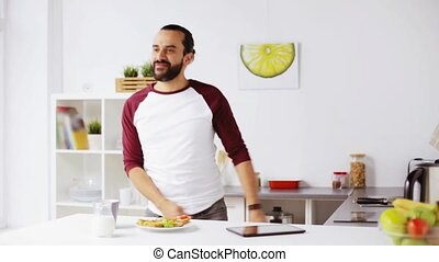 man eating breakfast and dancing at home - vegetarian food,...