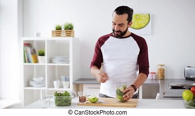 man with blender cooking smoothie at home kitchen - healthy...