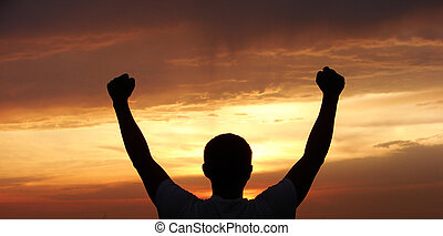 man - A man stands on against a sun with heaved up hands...