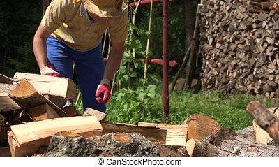 farmer split hard wood with axe in country near woodshed. 4K...